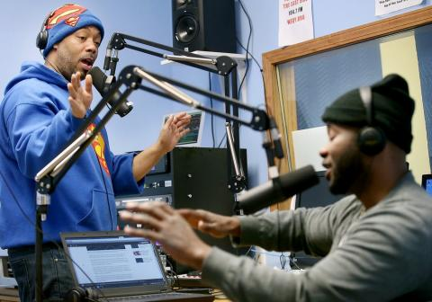 Shay Glorious Martin talks to Nick Muhammad in radio station studio.