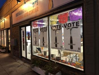 Indigenous Roots Cultural Arts center storefront at night with Vote posters