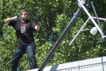 Photo of Will Floyd on roof holding wire attached to antenna pole.